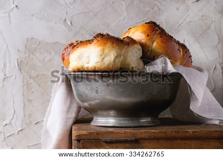 Close up of heap of sweet round sabbath challah bread with white and black sesame seeds in vintage metal bowl on wooden table with plastered wall at background. - stock photo