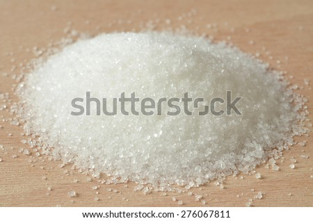 Close-up of heap of white granulated crystal sugar on wooden desk - stock photo