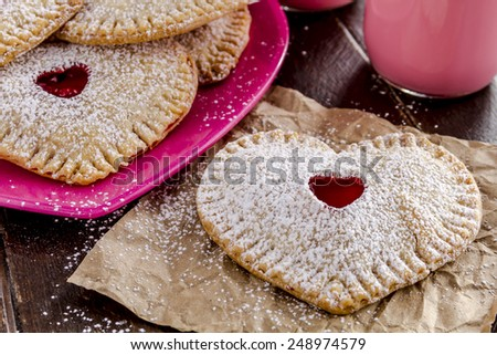 Close up of heart shaped cherry hand pies dusted with powdered sugar sitting on pink plate with glass of strawberry milk