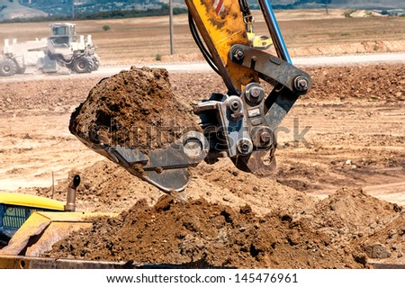 Close-up of heavy duty excavator scooping into earth and loading a dumper truck - stock photo