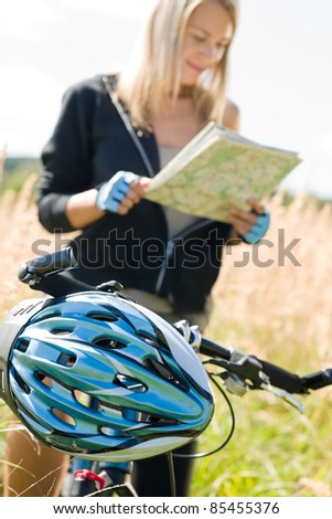 Close-up of helmet mountain biking young woman search in map - stock photo