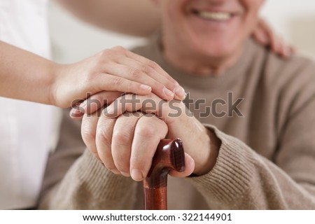 Close up of helpful carer hand and happy old man - stock photo