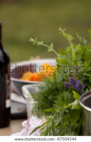 Close up of herb bouquet in the foreground; a bottle of wine and salad bowl with the chopped carrots in the background. Shallow depth of field. Focused on dill. - stock photo