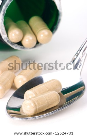 Close-up of herbal supplements capsules on spoon and open medication container. very shallow DOF - stock photo