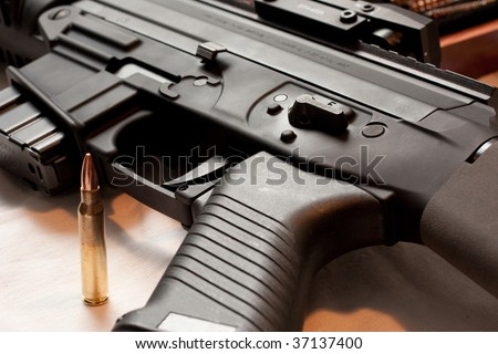 Close up of high power rifle upper and lower receiver with bullet in foreground - stock photo