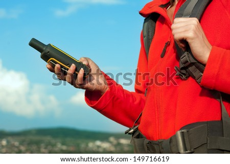 Close up of hiker young woman holding in her hand GPS navigator, Global Positioning System device - stock photo