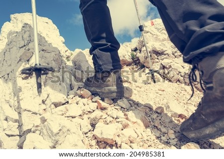Close up of hiking shoes and trekking poles ascending a mountain - stock photo