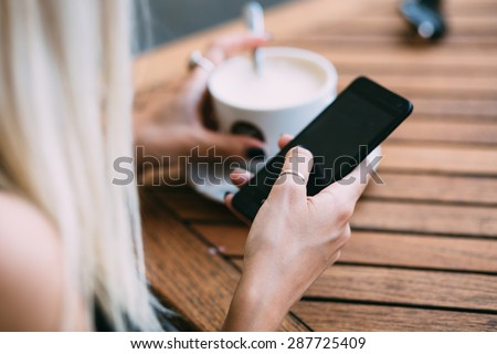 Close up of hip young woman using phone in cafe - stock photo