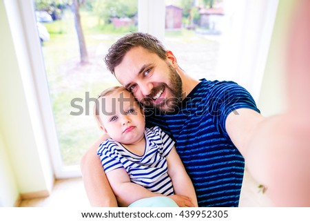 Close up of hipster father holding his little daughter