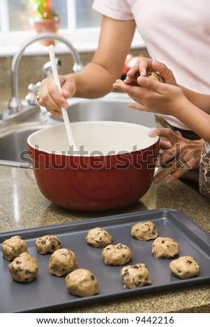 Close up of Hispanic mother and child in kitchen making cookies. - stock photo