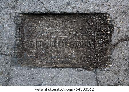 Close up of hole at damaged asphalt road - stock photo