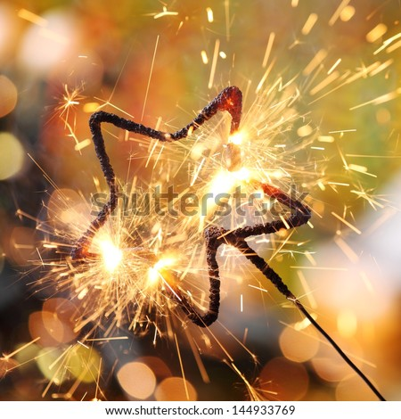 Close-up of holiday sparkler and defocused lights on background. - stock photo