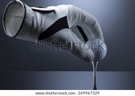 Close up of hollow golf glove putting ball on tee, isolated on dark blue background. - stock photo