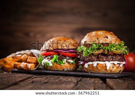 Close-up of home made burgers on wooden background - stock photo