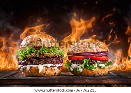 Close-up of home made burgers with fire flames. - stock photo
