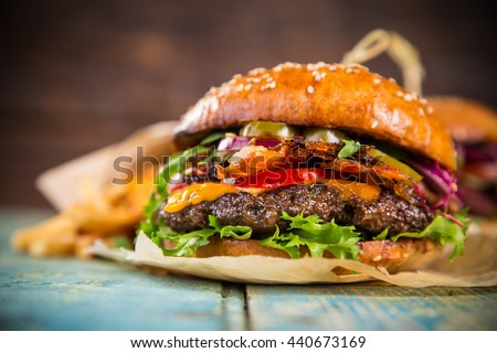 Close-up of home made tasty burger on wooden table. - stock photo