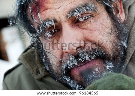 Close-up of homeless male face covered with frost - stock photo