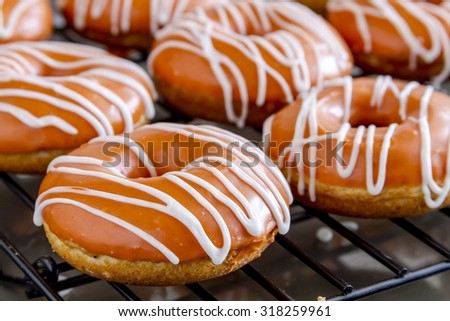 Close up of homemade baked pumpkin donuts with orange pumpkin glaze sitting on wire rack waiting for apple cider drizzle to dry - stock photo