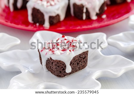 Close up of homemade chocolate brownie bite covered with white icing and candy cane sprinkles sitting on snowflake shaped plate - stock photo