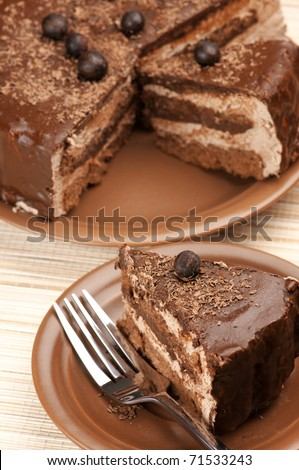 Close-up of homemade chocolate cake and fork on beige mat. - stock photo