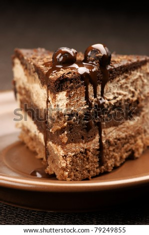 Close-up of homemade chocolate cake in brown ceramic plate. - stock photo
