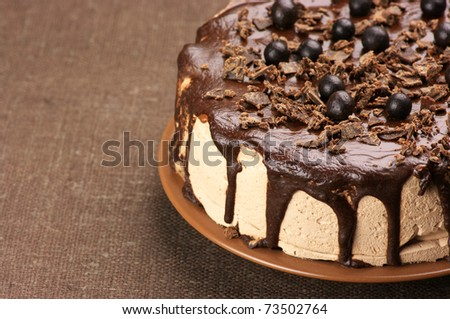 Close-up of homemade chocolate cake on brown canvas. - stock photo