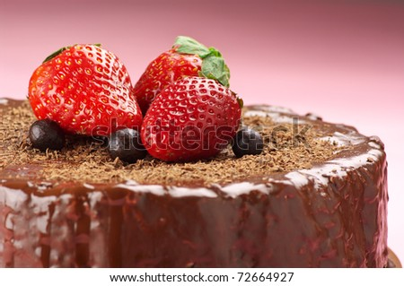 Close-up of homemade chocolate cake with strawberries on pink background. - stock photo
