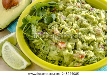 Close up of homemade chunky guacamole in bright green bowl sitting on blue napkin with lime wedges and avocado half