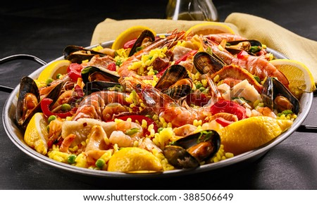 Close up of homemade delicious paella a la margarita in frying pan with black handles on dark table - stock photo