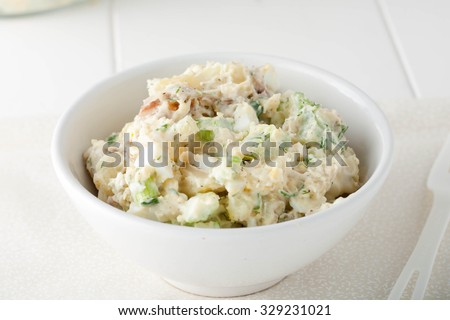 close up of homemade potato salad made with red potatoes, celery sticks, red onions and fresh herbs in white bowl - stock photo