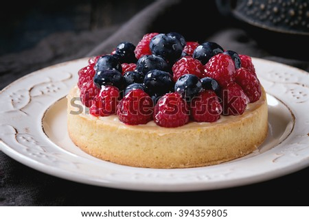 Close up of Homemade tart with custard, fresh raspberries and blueberries, served on white vintage plate with iron teapot on textile napkin over old wooden table. Dark rustic style - stock photo