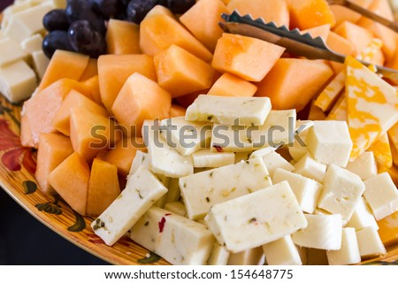 Close up of hors d'oeuvre platter of assorted cheeses and fruits - stock photo