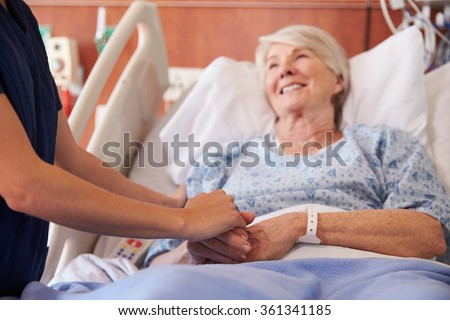 Close Up Of Hospital Nurse Holding Senior Patient's Hand - stock photo