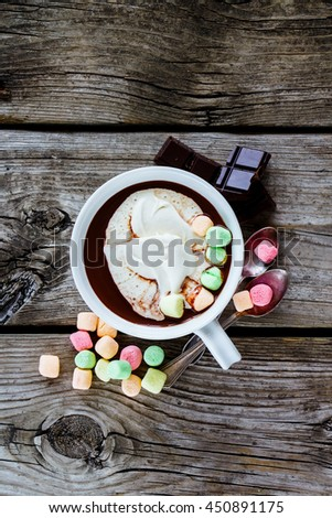 Close up of hot chocolate in white ceramic cup with whipped cream and marshmallows on rustic wooden background. - stock photo