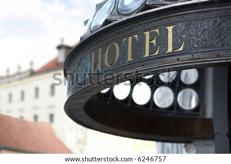 Close up of hotel header incription. Golden letters. Shallow DOF. - stock photo