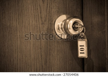 Close up of hotel key in door-handle lock. Shallow DOF. - stock photo
