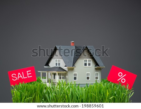 Close up of house model with green grass and sale tablets on grey background. Concept of real estate and building - stock photo
