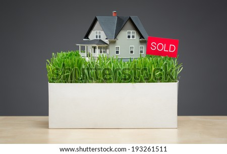 Close up of house model with green grass and sold tablet on grey background. Concept of real estate and sales - stock photo