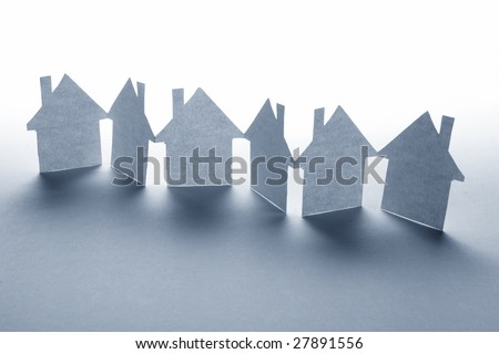 close up of houses cut out of paper on white background - stock photo