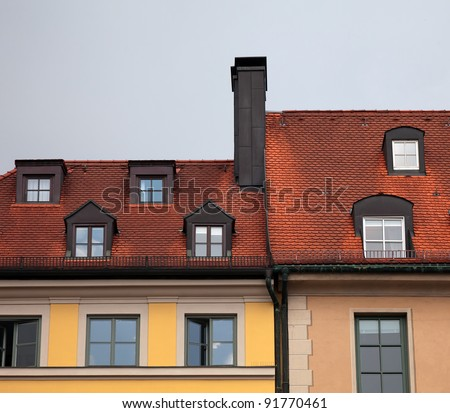 Close-up of  houses with red tile roof, chimney, attic, windows and downspout in Munich, Germany - stock photo