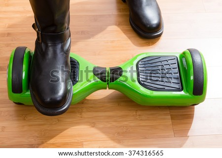 Close up of hoverboard from front top view with one of the riders feet on top and the other on wooden floor - stock photo