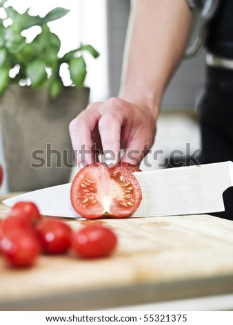 Close up of human cutting tomatoes - stock photo