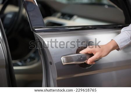 Close up of human female hand opening car door - stock photo