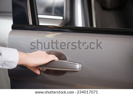 Close up of human female hand opening car door