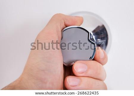 Close-up Of Human Hand Adjusting Water Meter - stock photo