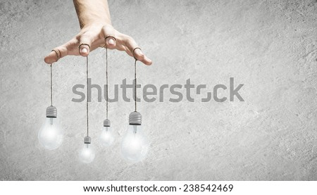 Close up of human hand and light bulbs hanging on finger - stock photo