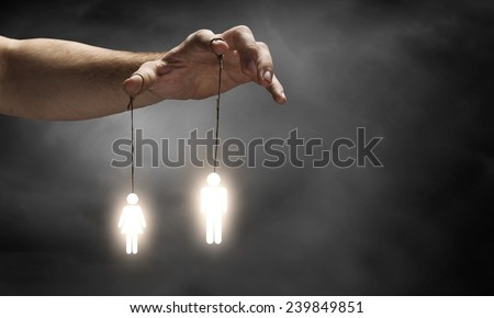 Close up of human hand and people hanging on fingers - stock photo