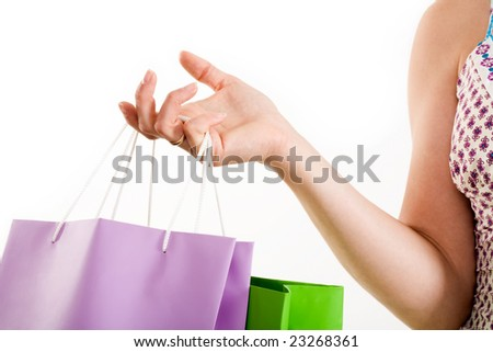 Close-up of human hand carrying shopping bags over white background - stock photo