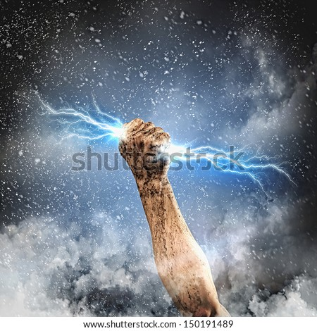 Close-up of human hand clenching lightning flash - stock photo