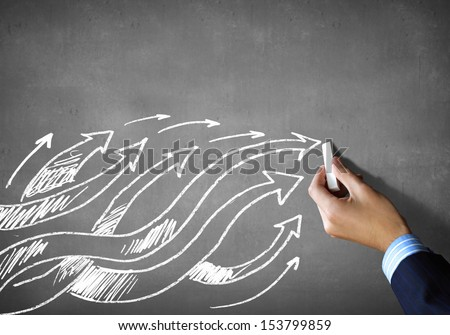Close up of human hand drawing arrows - stock photo